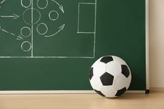Soccer ball near chalkboard with football game scheme. On table stock image