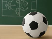Soccer ball near chalkboard with football game scheme. On table. Space for text stock images