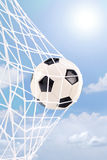 Soccer ball in a net against cloudy sky Royalty Free Stock Image