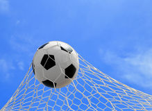 Soccer ball in net. On blue sky Royalty Free Stock Image