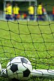 Soccer ball in net at field. A soccer ball stuck in a football net while there is a soccer match going on with kids wearing yellow jerseys Stock Images