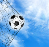 Soccer ball in the net gate. On a sky background royalty free stock photos