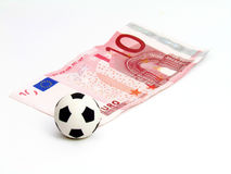 Soccer Ball in note 10 euro. Soccer ball over the corner of a 10 euro note on a white background Royalty Free Stock Photography
