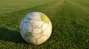 Soccer ball. Old worn soccer ball on the green grass Royalty Free Stock Images