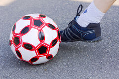 Soccer ball and one leg of the athletes in the sneakers Stock Image