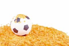Soccer ball on orange confetti Stock Photos