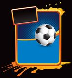 Soccer ball on orange splattered advertisement Royalty Free Stock Photography