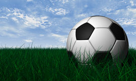 Soccer ball over green grass. Soccer ball render over green grass and blue sky Royalty Free Stock Photography