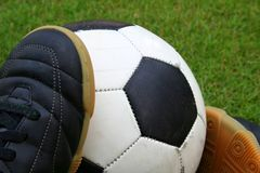 A soccer ball and a pair of shoes. A worn-out soccer ball with a pair of futsal shoes on grass Stock Images
