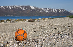 Soccer ball on pebble beach Stock Images