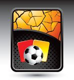 Soccer ball and penalty cards on cracked backdrop Royalty Free Stock Images