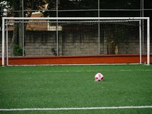 A soccer ball with pink spots placed on the penalty kick point with no one on the goal line royalty free stock photo