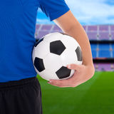 Soccer ball in player's hand on field of big stadium Royalty Free Stock Photo