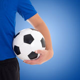 Soccer ball in player's hand over blue Stock Photo