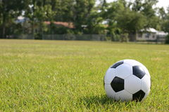 Soccer ball in playing field. Close-up of soccer ball laying in green playing field Stock Photography