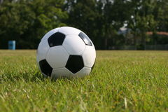 Soccer Ball in playing field. Close-up of soccer ball in green playing field Royalty Free Stock Photography