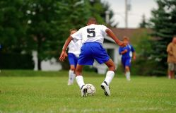 Soccer Ball Pose. A teenager handles a soccer ball in a match. Right hand and feet have very slight action blur Royalty Free Stock Photo