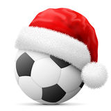 Soccer ball in red Santa Claus hat Stock Images