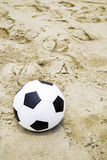 Soccer ball on the sand Stock Photography
