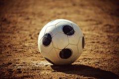 Soccer ball on sand field Stock Photo
