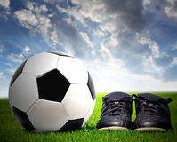Soccer ball and shoes. In grass Royalty Free Stock Photography