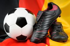 Soccer ball and shoes on German flag. Shiny soccer shoes and ball nicely arranged on the German flag Royalty Free Stock Photography