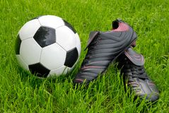 Soccer ball and shoes on grass. Closeup of a shiny soccer ball and black soccer shoes on fresh grass royalty free stock photography