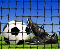 Soccer ball and shoes. In grass Stock Image
