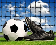 Soccer ball and shoes. In grass Royalty Free Stock Photos