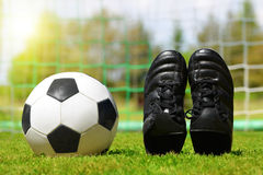 Soccer ball and shoes in grass. Soccer ball and shoes on football playground Stock Photo