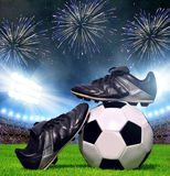 Soccer ball and shoes in grass Stock Photo