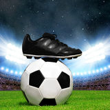 Soccer ball and shoes in grass Stock Photography