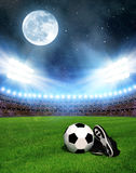 Soccer ball and shoes in grass Royalty Free Stock Photography