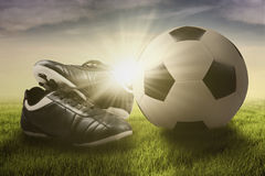 Soccer ball and shoes on the meadow Stock Photography