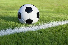 Soccer ball sits on grass field with white stripe. A traditional soccer ball sits on a grass field with white stripe Royalty Free Stock Photography