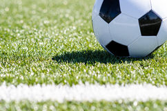 Soccer ball sitting in grass close to line Stock Photography
