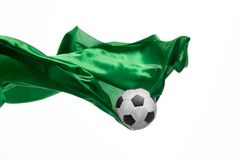 Soccer ball and Smooth elegant transparent green cloth isolated or separated on white studio background. Texture of flying fabric. Attributes of popular game royalty free stock photo