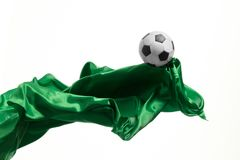 Soccer ball and Smooth elegant transparent green cloth isolated or separated on white studio background. Texture of flying fabric. Attributes of popular game stock image