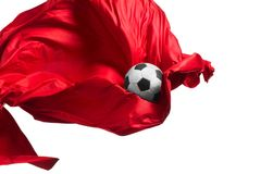 Soccer ball and Smooth elegant transparent red cloth isolated or separated on white studio background. Texture of flying fabric. red. Attributes of popular royalty free stock photo