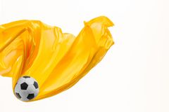 Soccer ball and Smooth elegant transparent yellow cloth isolated or separated on white studio background. Texture of flying fabric. yellow. Attributes of stock images