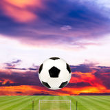 Soccer ball with soccer field against beautiful sunset. Background Royalty Free Stock Photos