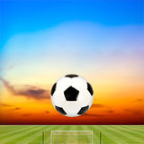 Soccer ball with soccer field against beautiful sunset. Background Royalty Free Stock Image