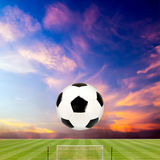 Soccer ball with soccer field against beautiful sunset Royalty Free Stock Image