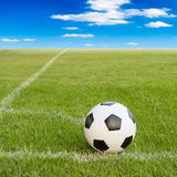 Soccer ball on soccer field against blue sky Stock Images