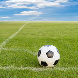 Soccer ball on soccer field against blue sky Stock Image