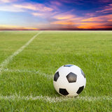 Soccer ball on soccer field against sunset sky Royalty Free Stock Photo