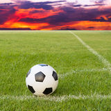 Soccer ball on soccer field against sunset sky Royalty Free Stock Photos