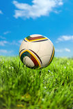 Soccer ball on soccer field. Soccer ball on grass and sky background Stock Image
