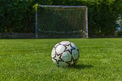 Ball on a green lawn in front of a football goal. Soccer ball and soccer goal,ball on a green lawn in front of a football goal Stock Photography