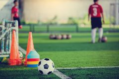 Soccer ball and soccer training equipment on green artificial turf. With blurry of soccer players training. Soccer Academy royalty free stock photography